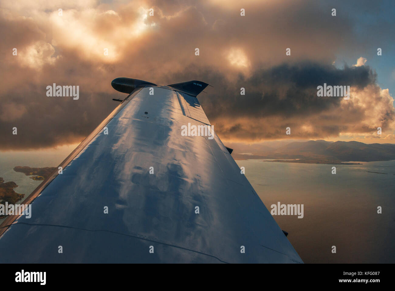 Close up detail of the wing of a Pilatus PC12 aircraft against a sunset cloudscape. - Stock Image