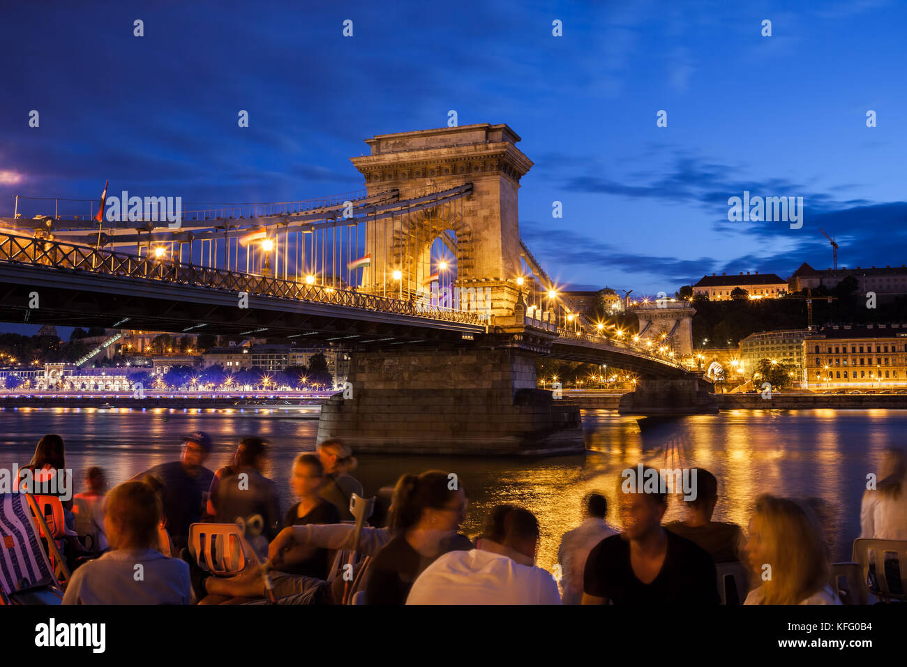 Budapest by night in Hungary, city break, group of people hangout and chill out at Danube river next to Szechenyi - Stock Image