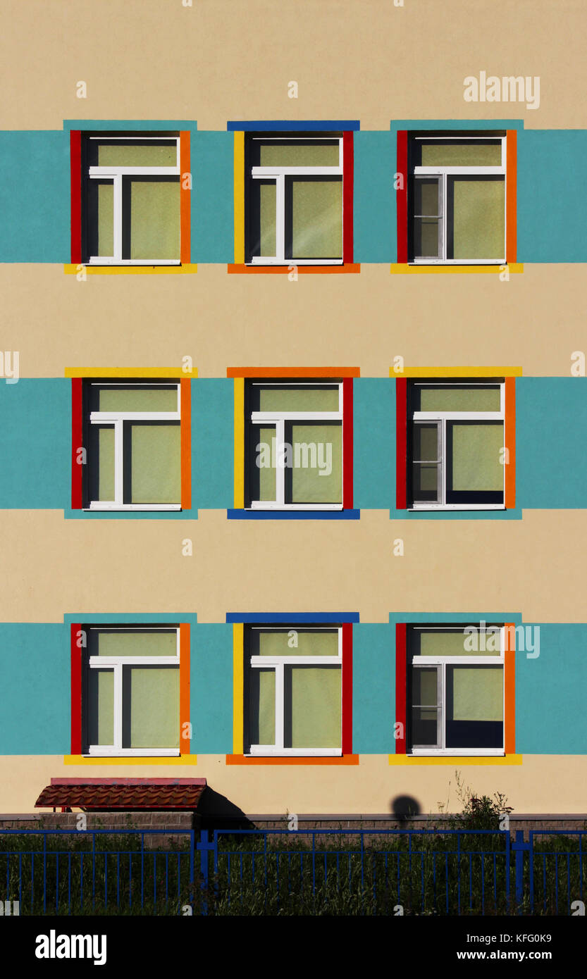 nice colorful house a kindergarten for children. nine windows, blue, yellow and beige color - Stock Image