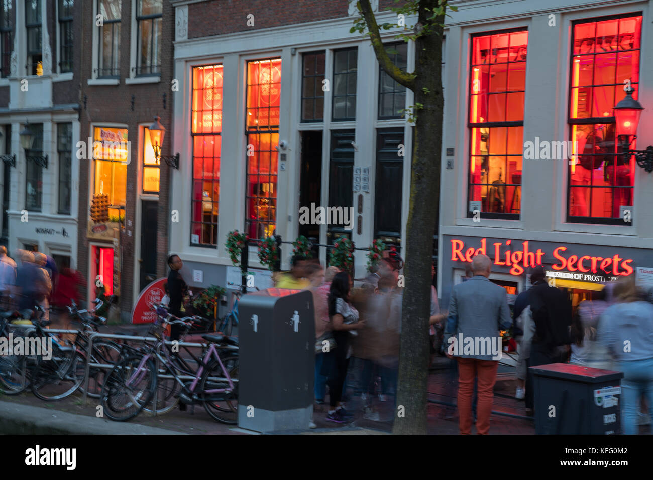 AMSTERDAM, HOLLAND - AUGUST 17, 2017;  People and night lights along canal in red light district outside Red Light - Stock Image