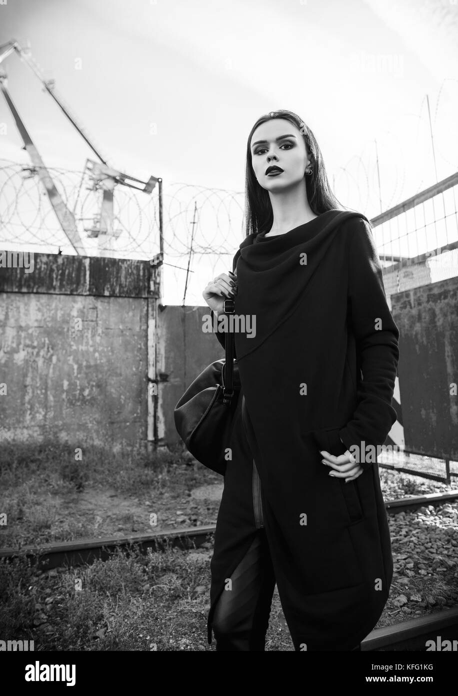 Portrait of the beautiful rock girl (informal model) in tunic and leather pants standing in industrial area. Black and white Stock Photo