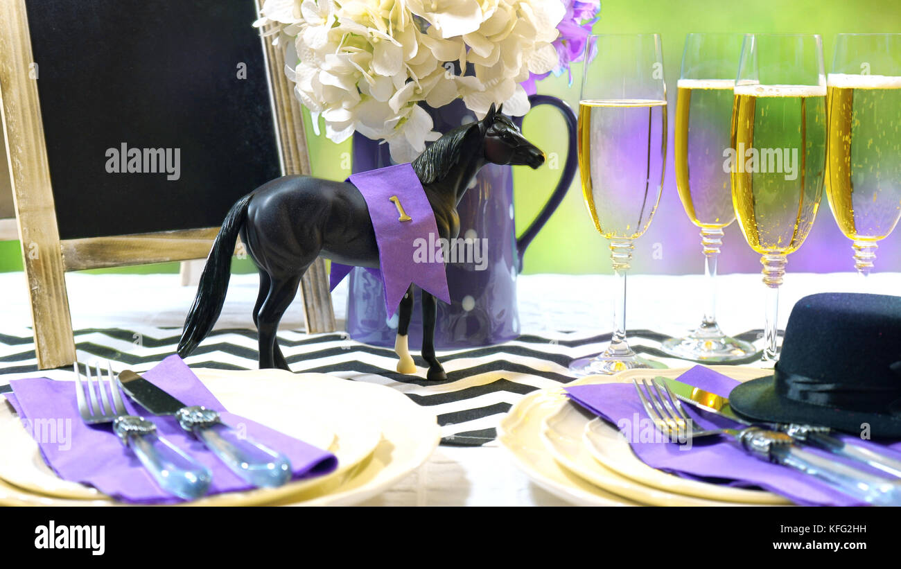 Horse racing Racing Day Luncheon fine dining table setting with small black fascinator hat, decorations and champagne. - Stock Image