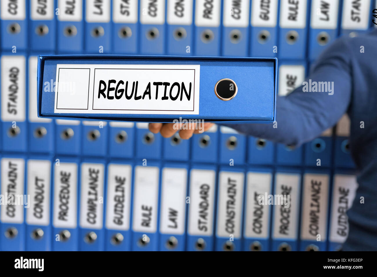 Regulation Business Concept. Young man holding ring binder. - Stock Image
