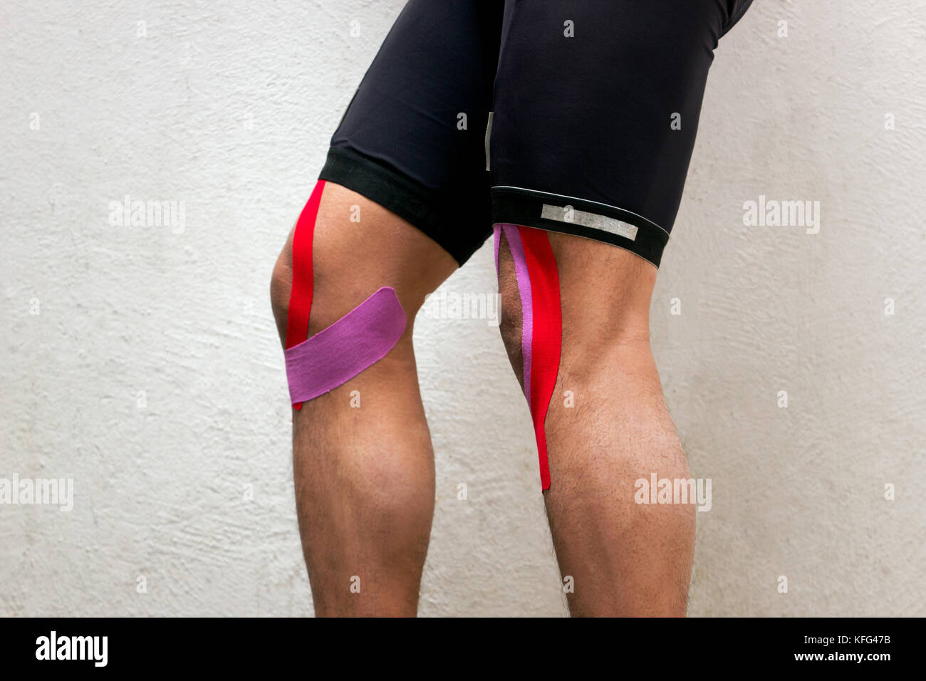 Horizontal photo of a male cyclist with kinesio tape on his knees standing in front of a white background pointing - Stock Image