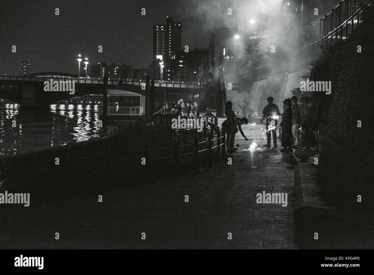 People setting off fireworks by the waters edge in Asakusa, Tokyo. Stock Photo