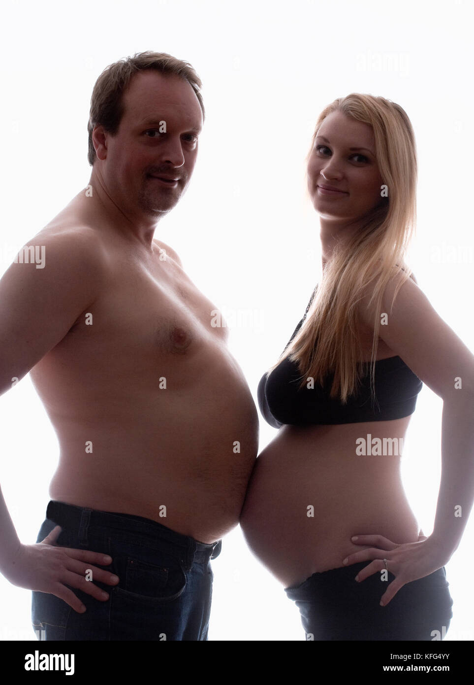 Pregnant Woman and her Partner Measuring Bellies. - Stock Image