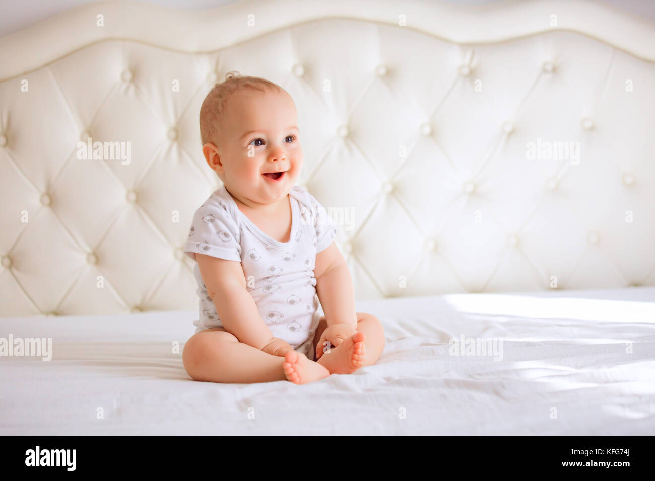 Adorable baby boy in white sunny bedroom. Newborn child relaxing in bed. Nursery for young children. Textile and - Stock Image