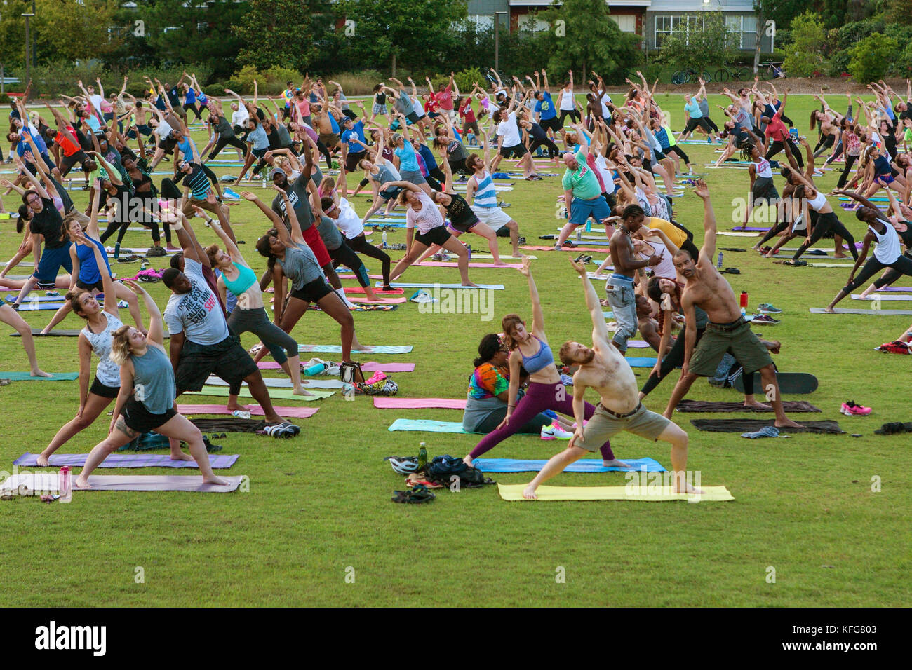 Atlanta, GA, USA - July 2, 2017:  Dozens of people stretch doing a yoga pose as they take part in a free group yoga - Stock Image