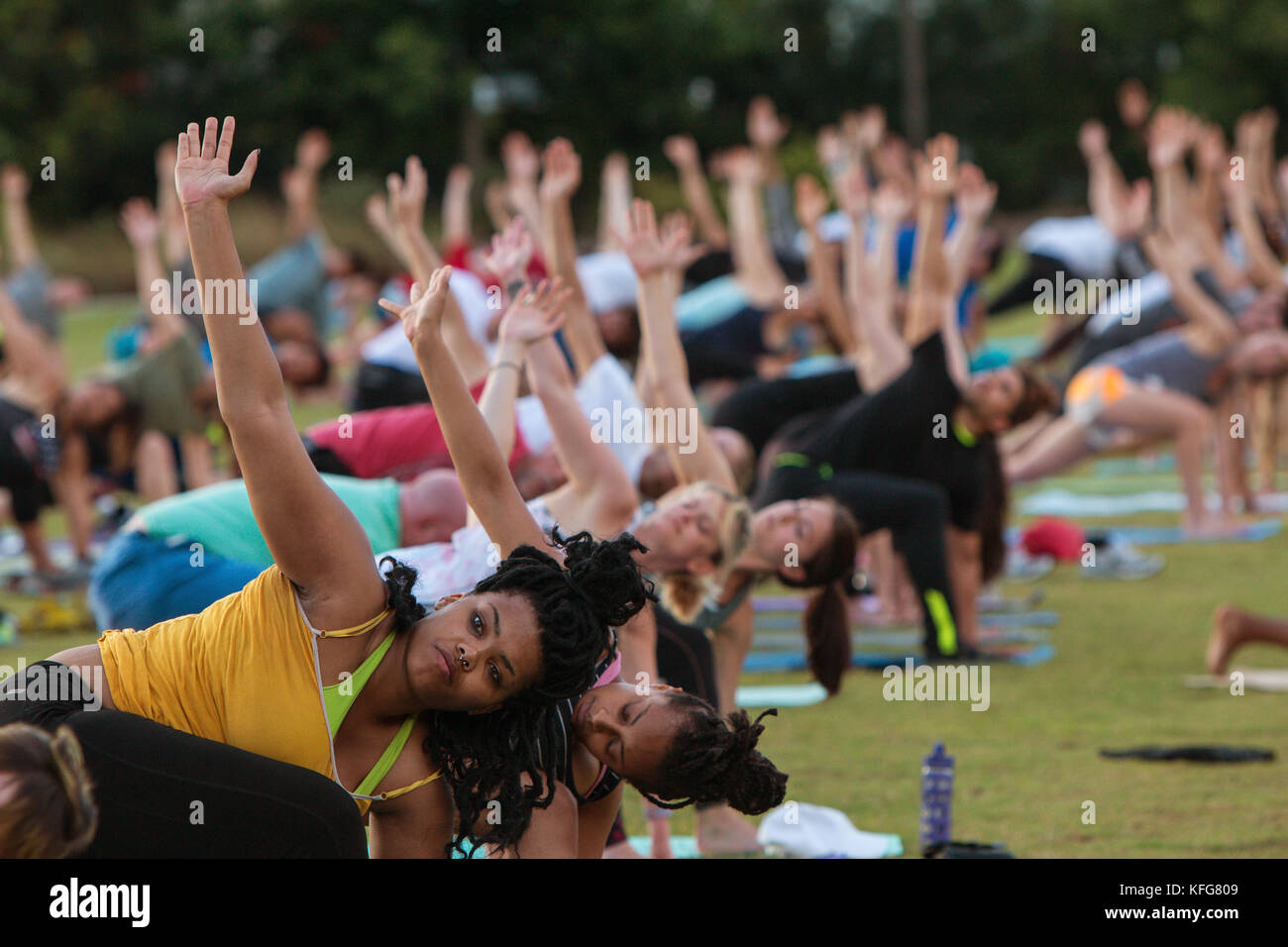 Atlanta, GA, USA - July 2, 2017:  Dozens of people do the triangle yoga pose as they take part in a free group yoga - Stock Image