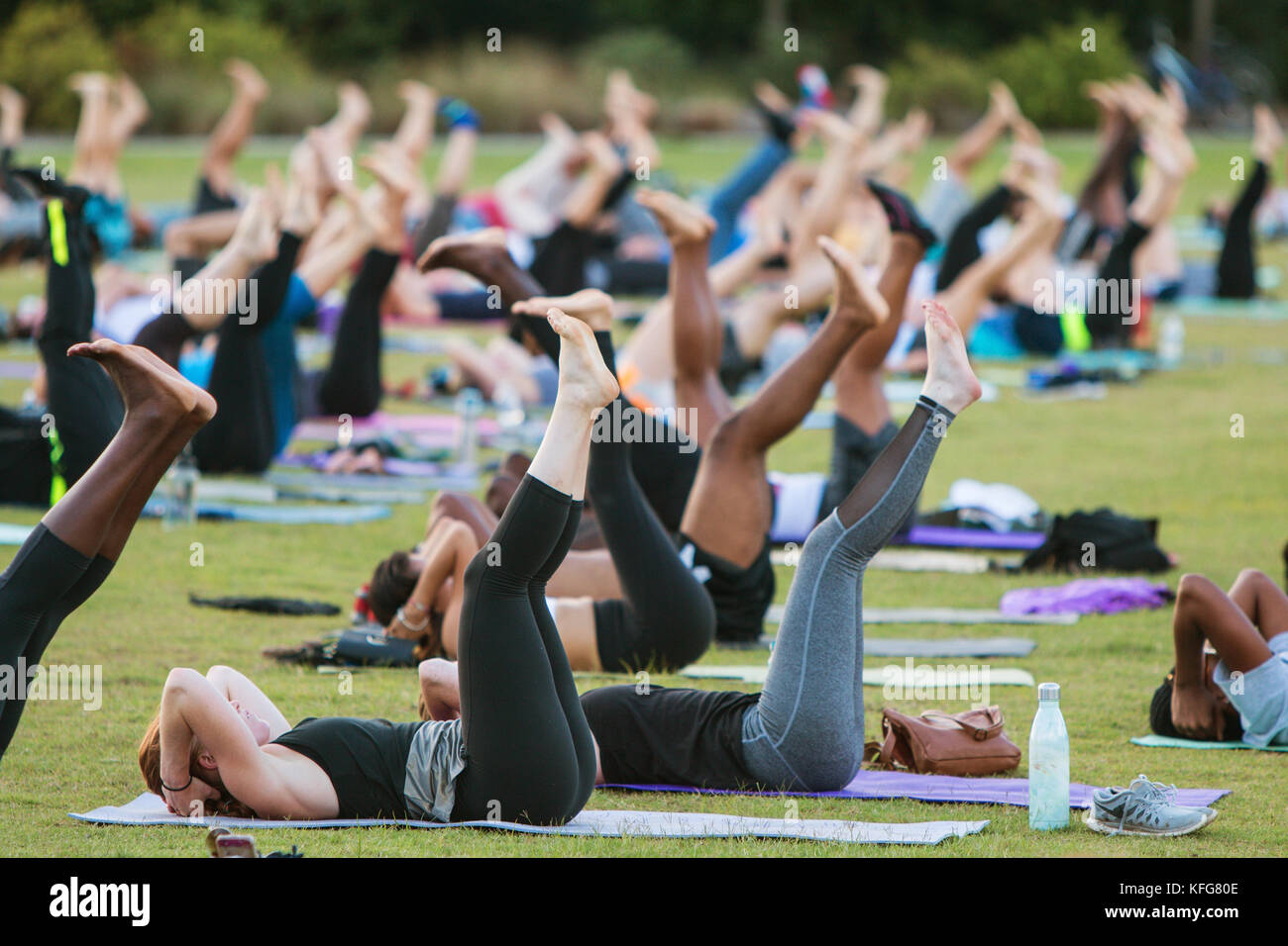 Atlanta, GA, USA - July 2, 2017:  Dozens of people do a yoga pose lying on their backs as they take part in a free - Stock Image
