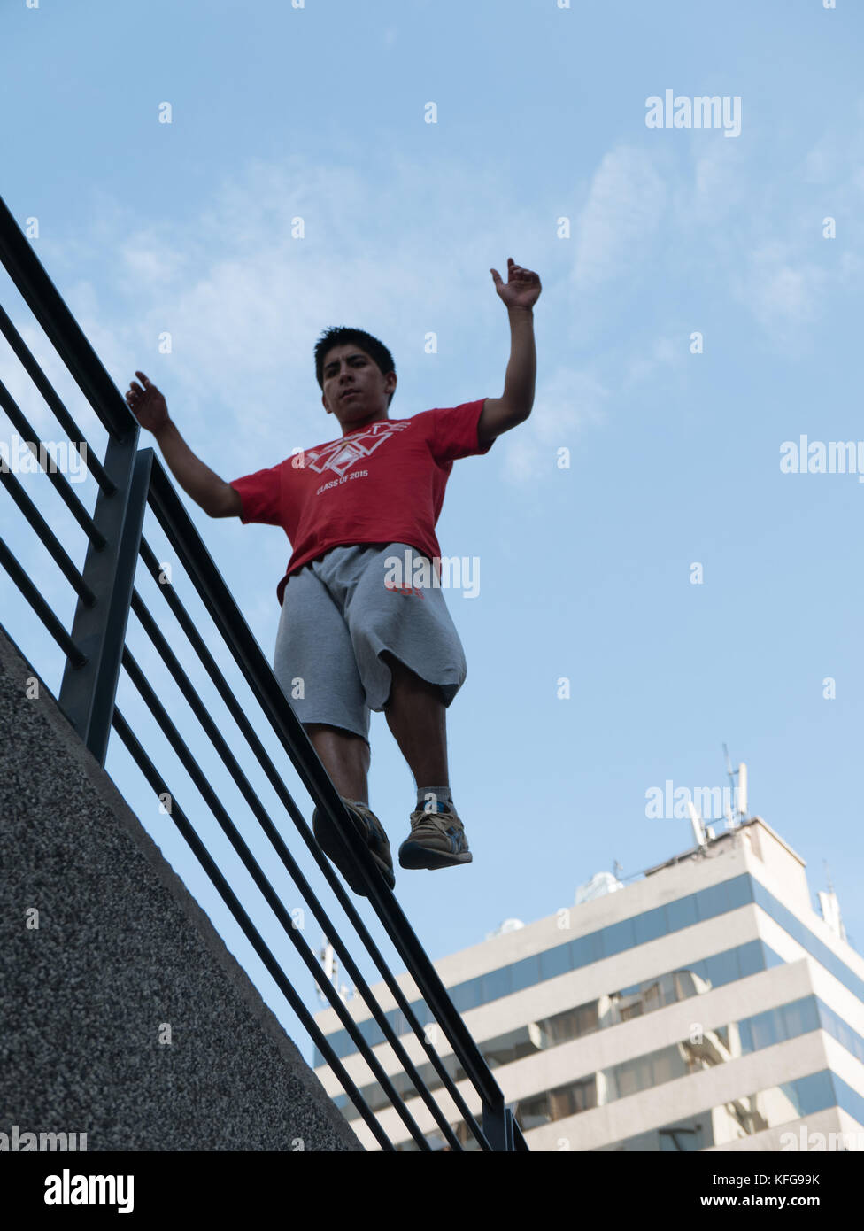 Young man in Santiago Chile engaged in parkour by balancing on a handrail high above the ground with blue sky and - Stock Image