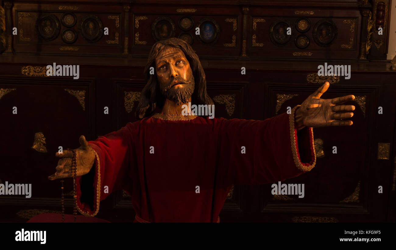 Dramatically light statue of Christ in red robe with outstretched hands holding a rosary with a look of pain and - Stock Image