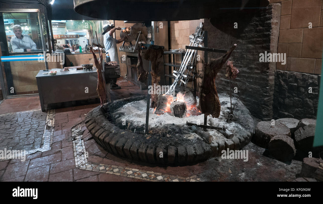 Traditional Argentinian open flame fire cooking splayed beef, chunks of wood in foreground with chef cutting meat - Stock Image