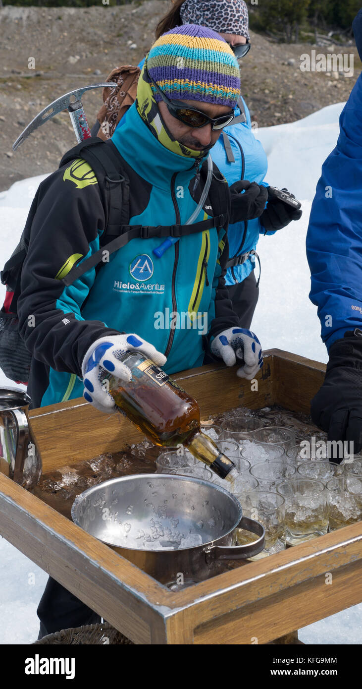 Local tour guide poring small glasses of whiskey over glacier ice at end of hiking on glacier.  Bottle in hand with - Stock Image