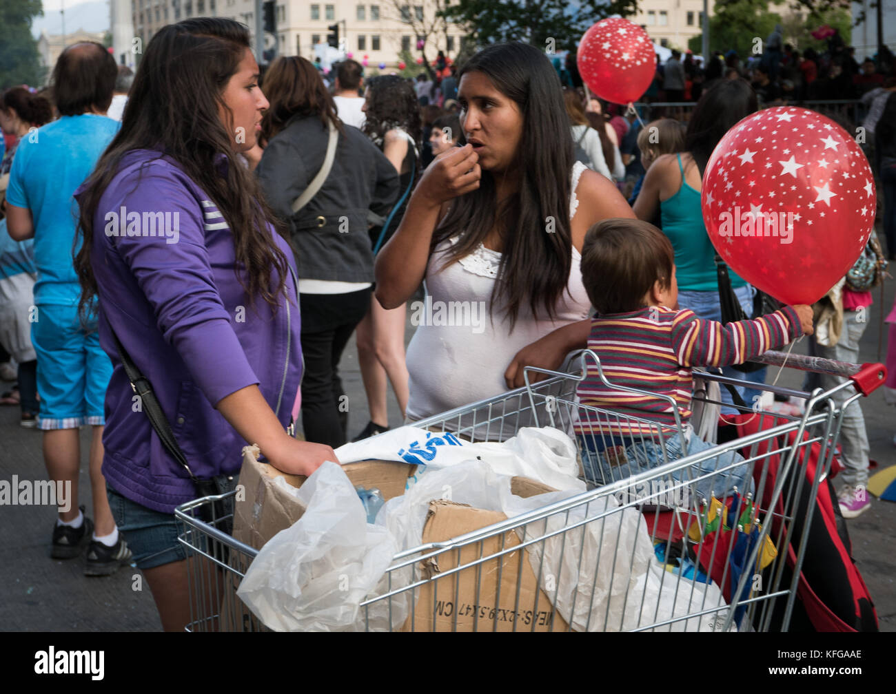 Two young women with baby in shopping cart with red Christmas balloons smoking a joint during a Christmas parade - Stock Image
