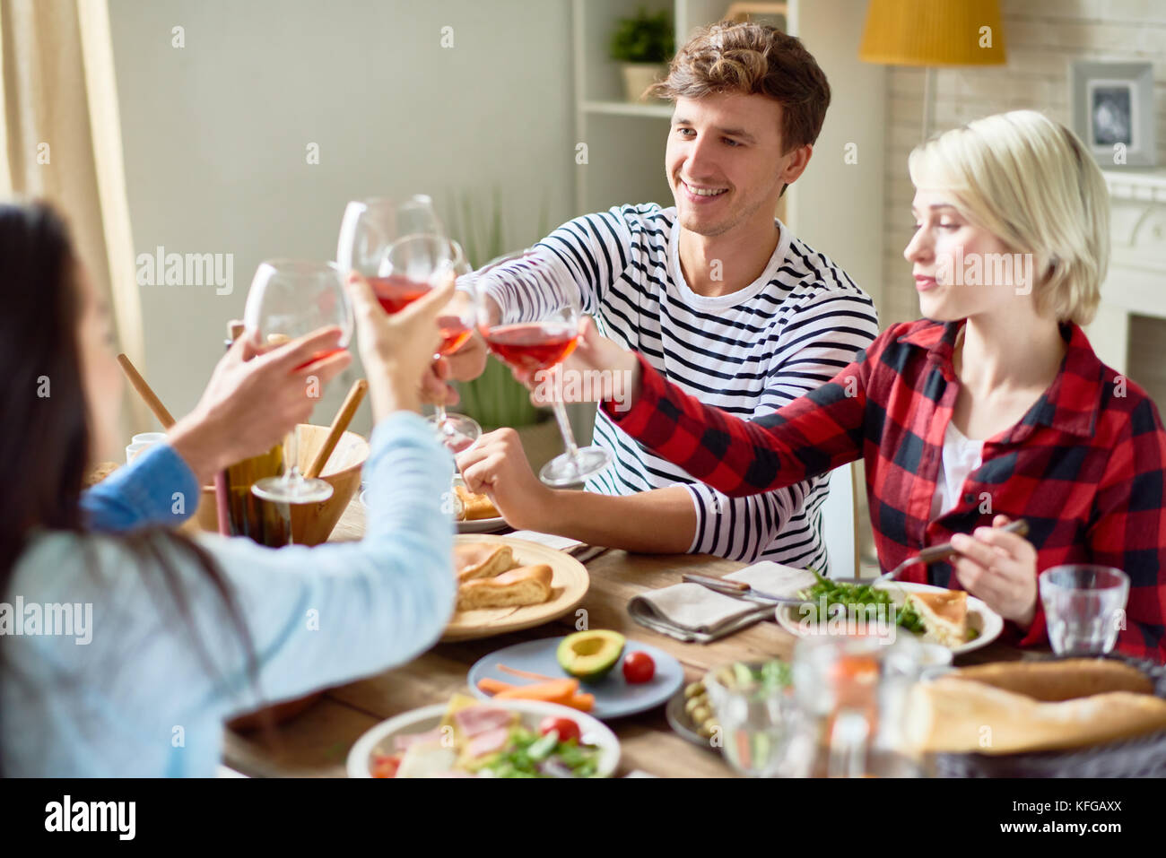 Friends Clinking Glasses at Dinner Party - Stock Image
