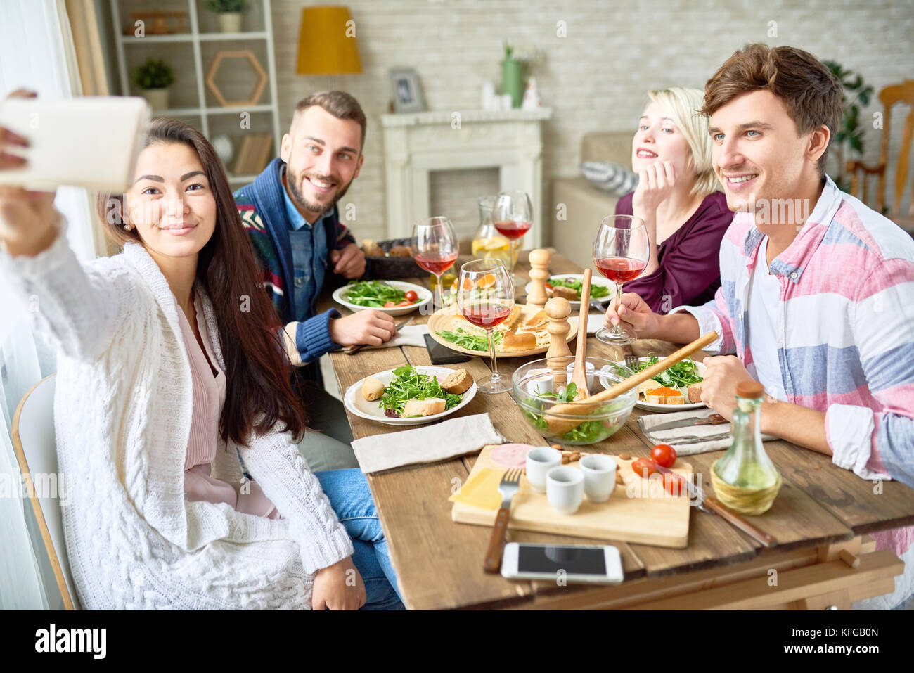 Friends Taking Selfie at Dinner Table - Stock Image
