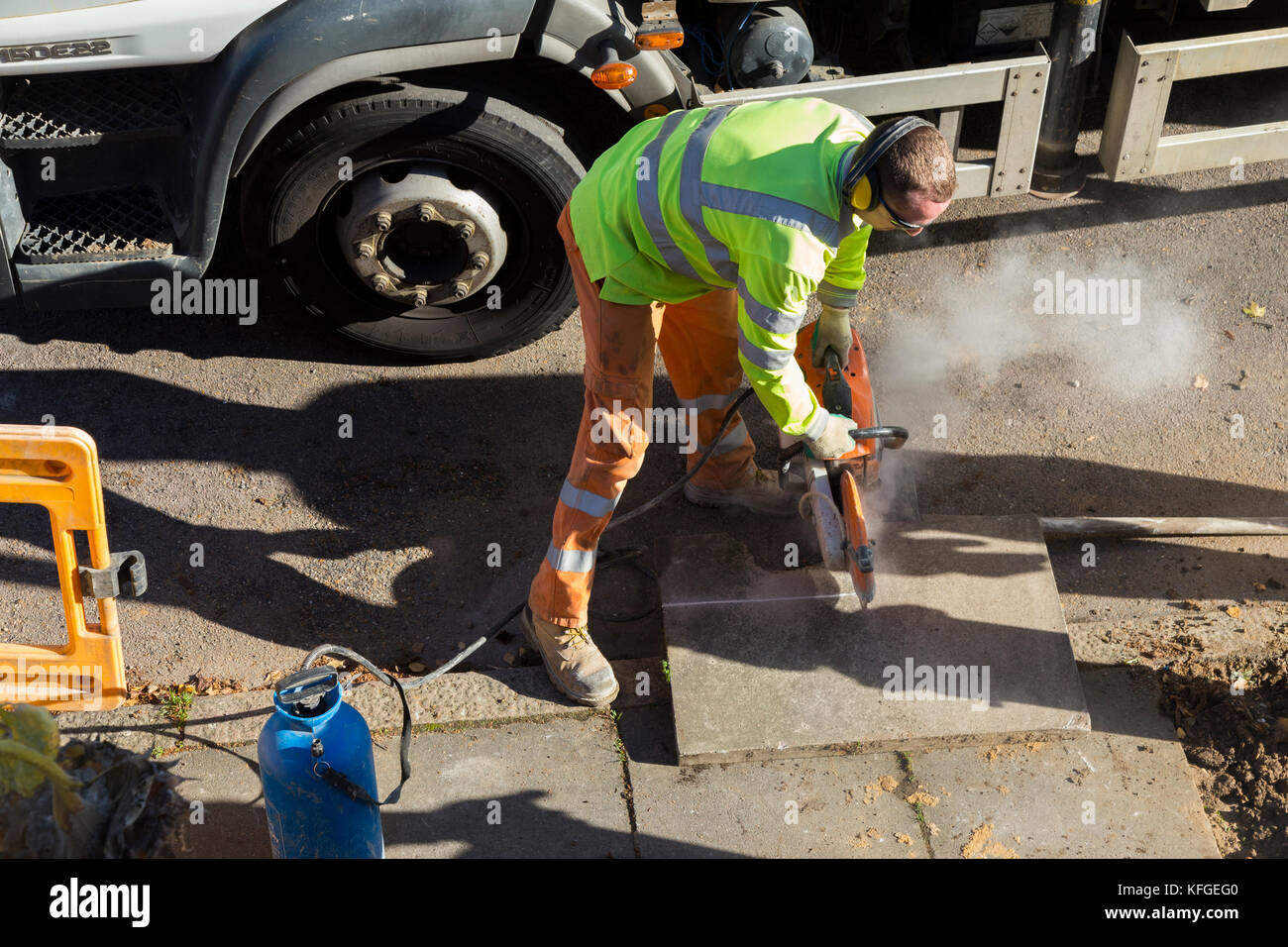 Team of lighting contractors reinstate pavement and cut concrete slabs to size with an angle grinder after fitting - Stock Image
