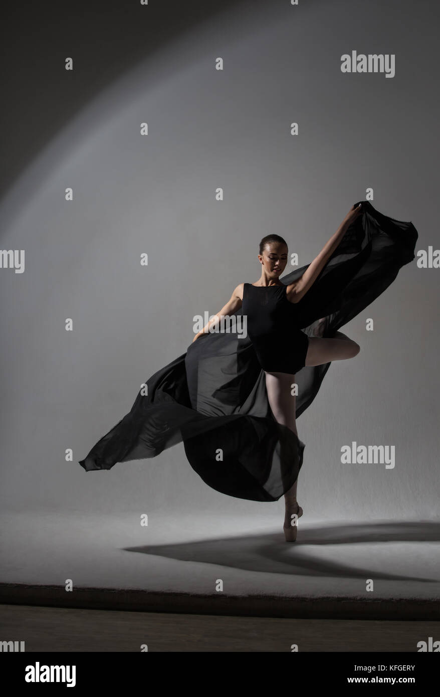 Graceful ballerina with black cloth whirling in the dance - Stock Image