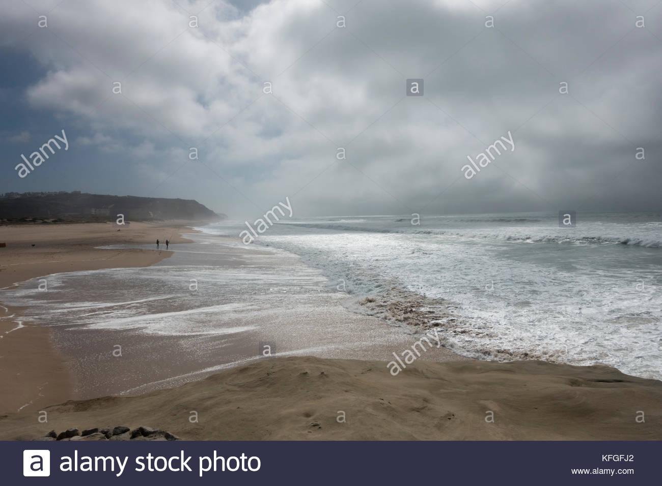 dark rain clouds coming inland from the Atlantic Ocean, Praia da Areia Branca Portugal - Stock Image