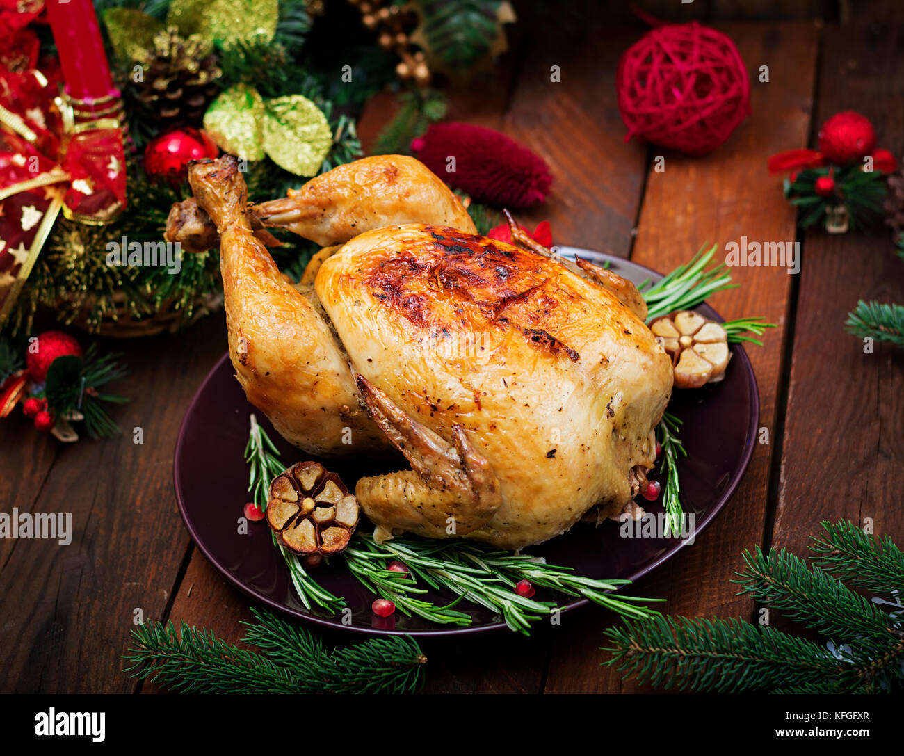 Baked turkey or chicken. The Christmas table is served with a turkey, decorated with bright tinsel and candles. - Stock Image