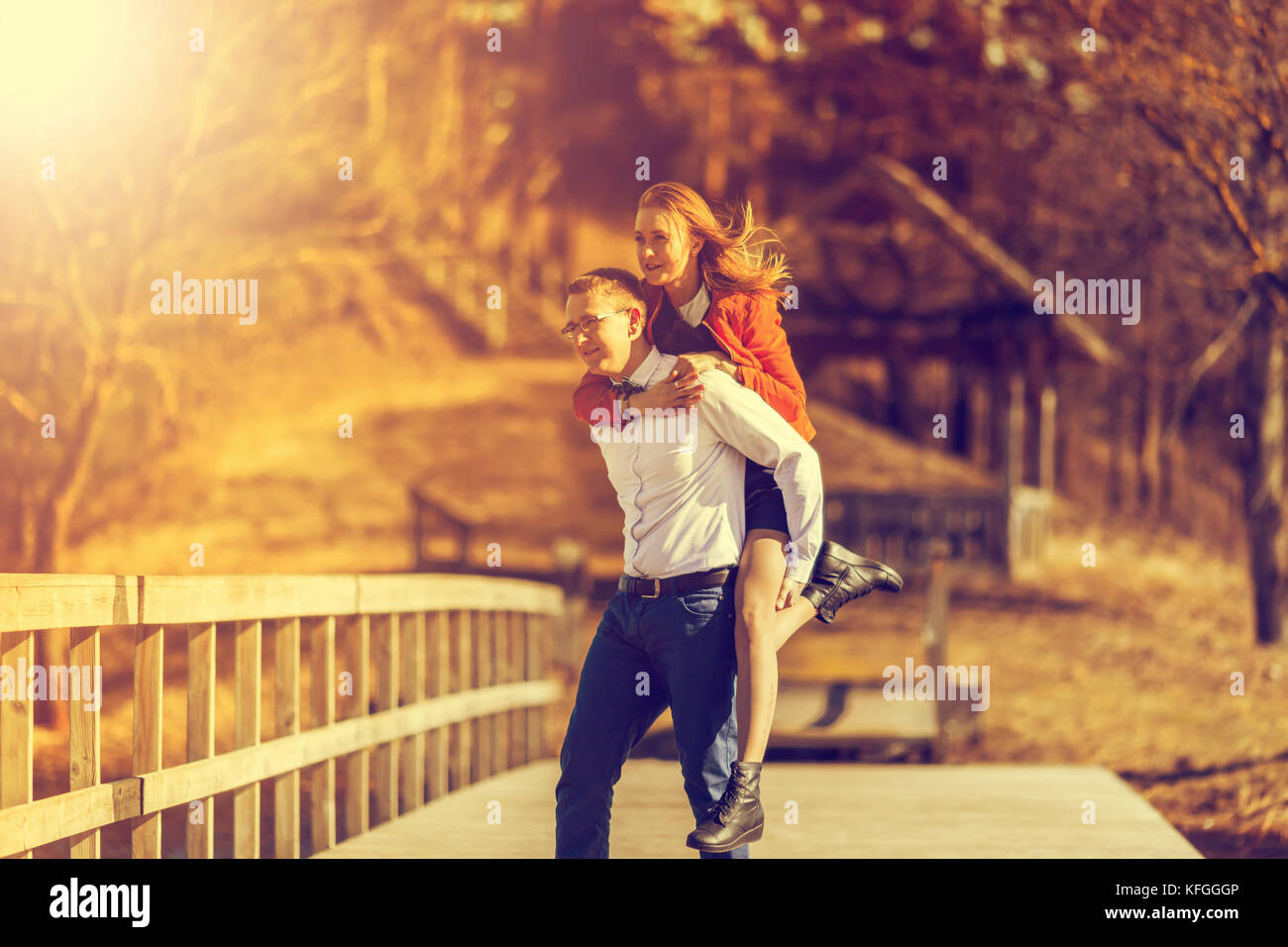 Happy man carrying his girlfriend on the back on on the bridge over the river. Vintage tone - Stock Image