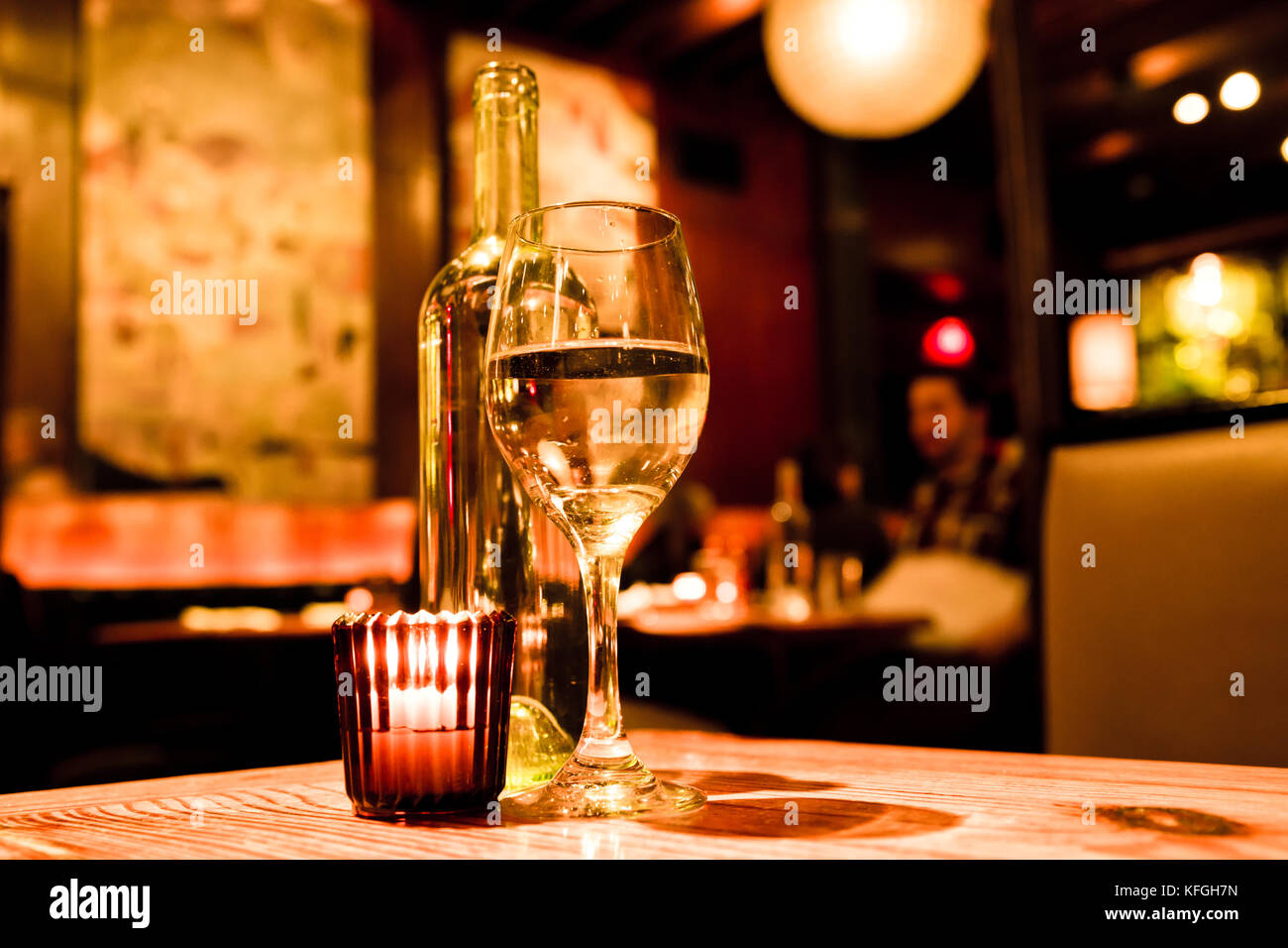 Wine glass, bottle and candle on table in restaurant with warm light - Stock Image