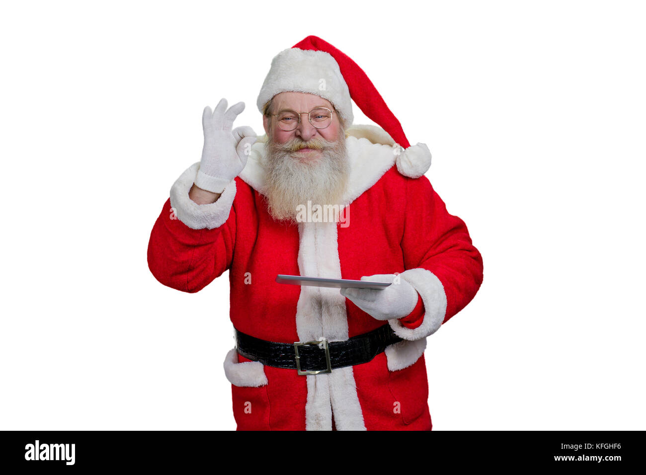 Santa Claus with digital tablet. Senior Santa Claus is realizing kids wishes making a magic on white background. - Stock Image
