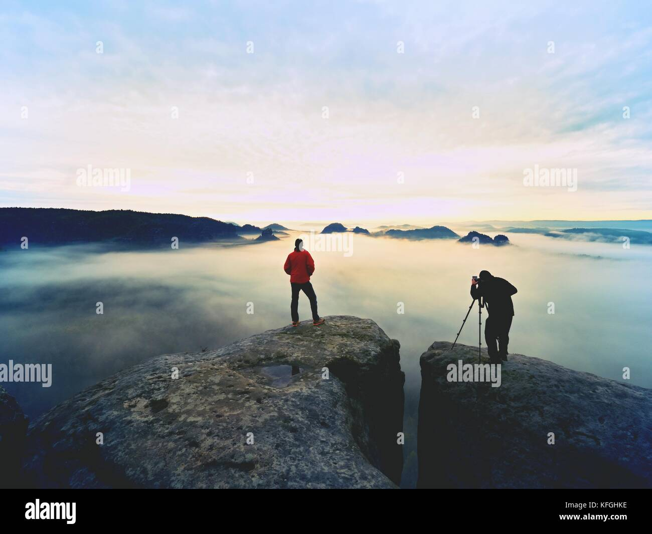 Silhouettes of man photographers. Men on mountain. Peak  with two men taking photos in autumn morning sunrise - Stock Image
