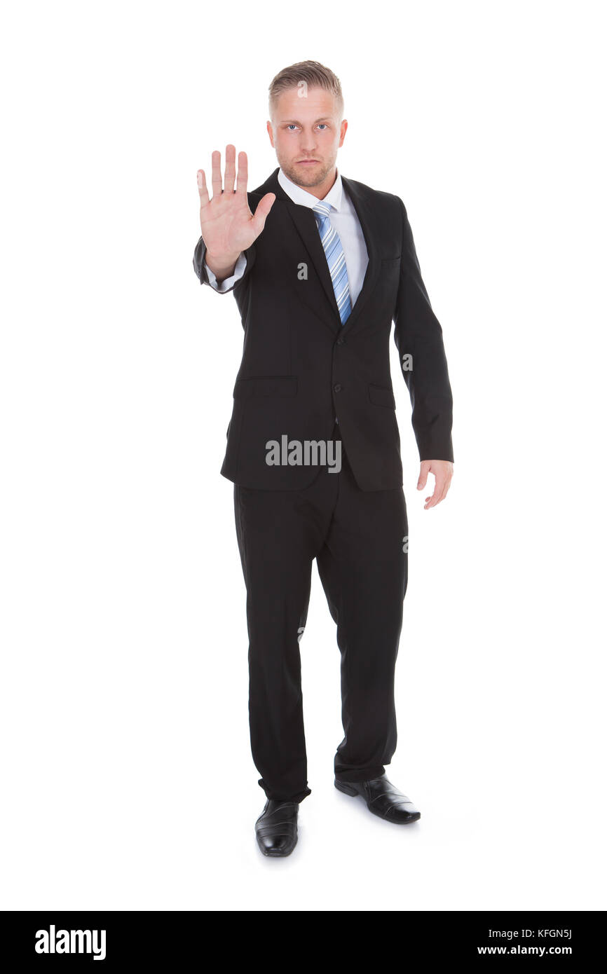 Handsome bearded businessman holding up his hand in a stop or halt gesture as he forbids entry or brings something - Stock Image