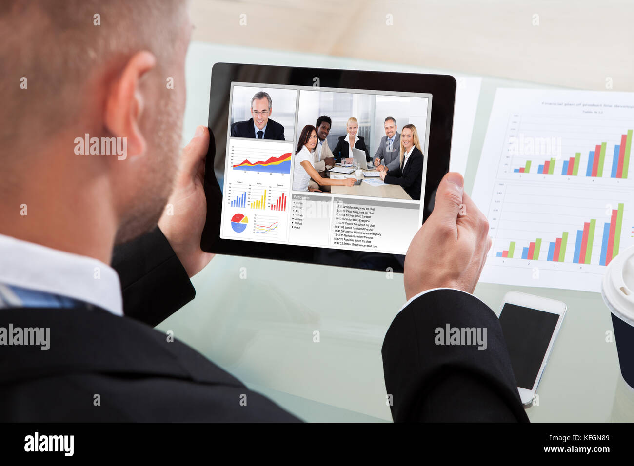 Businessman on a video or conference call on his tablet with an image of work colleagues in a meeting and bar graphs - Stock Image