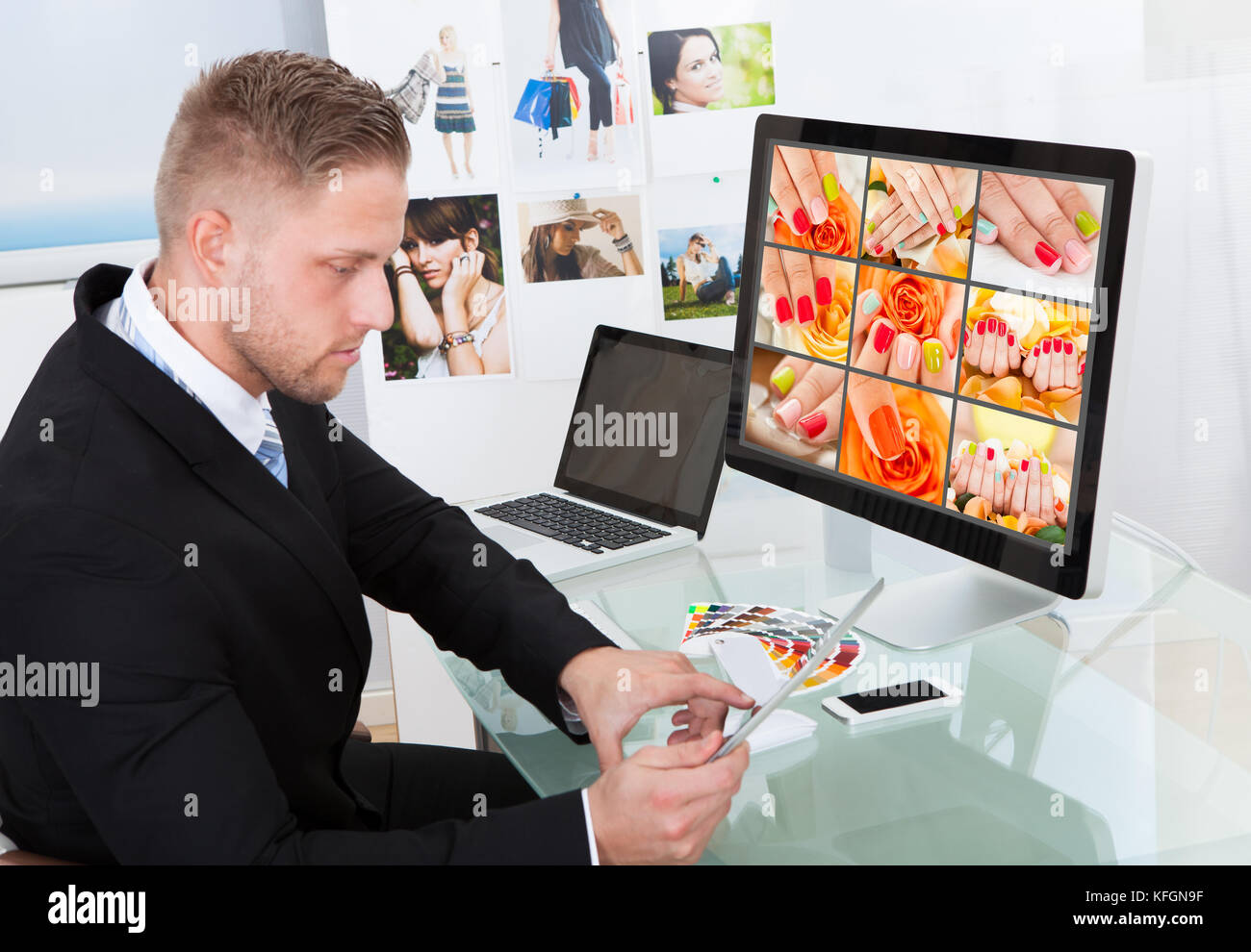 Businessman sitting at his desk in front of a large screen monitor editing photographs - Stock Image