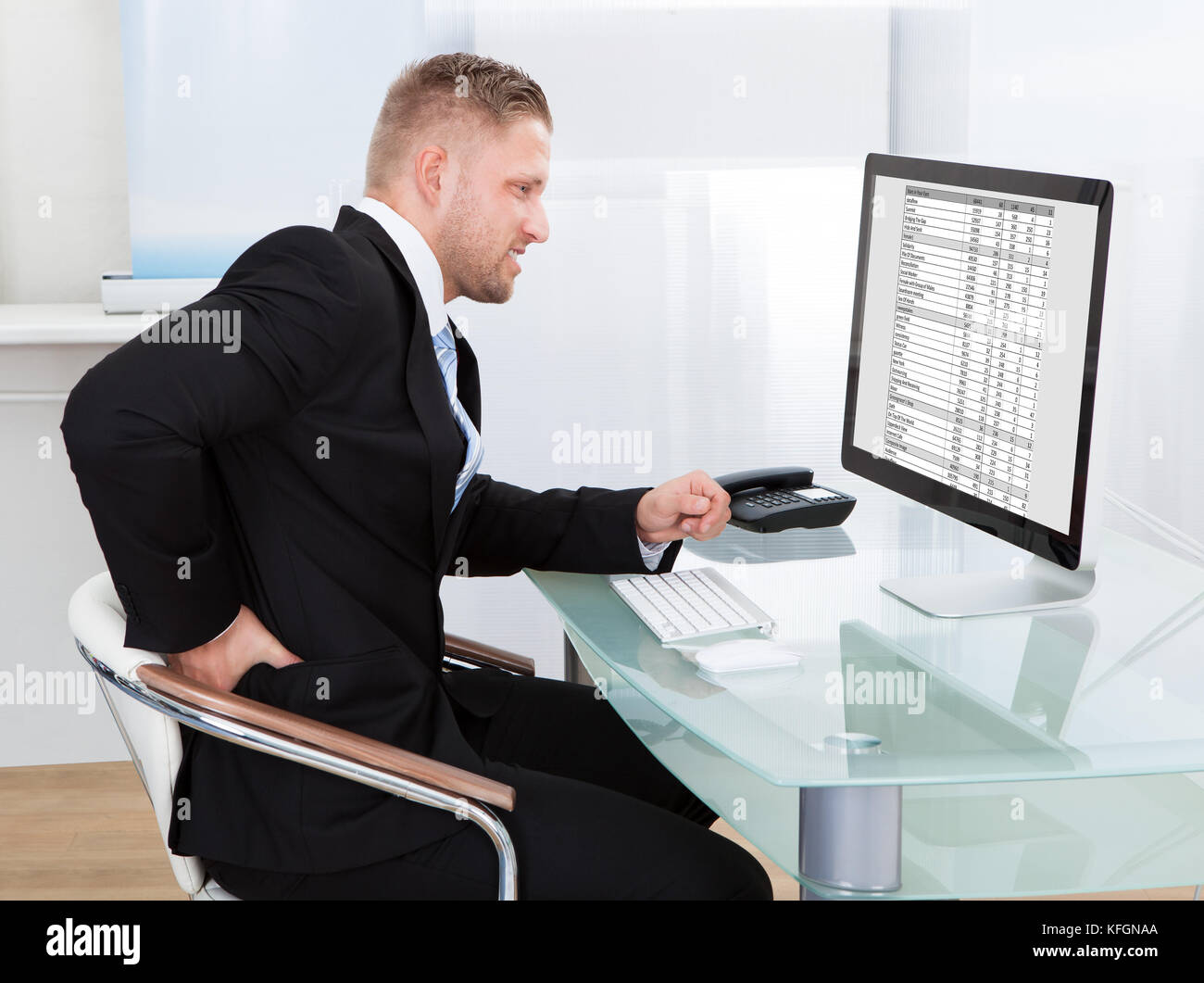 Businessman rubbing his back as he sits working at his desk in font of his large desktop monitor as he eases the - Stock Image