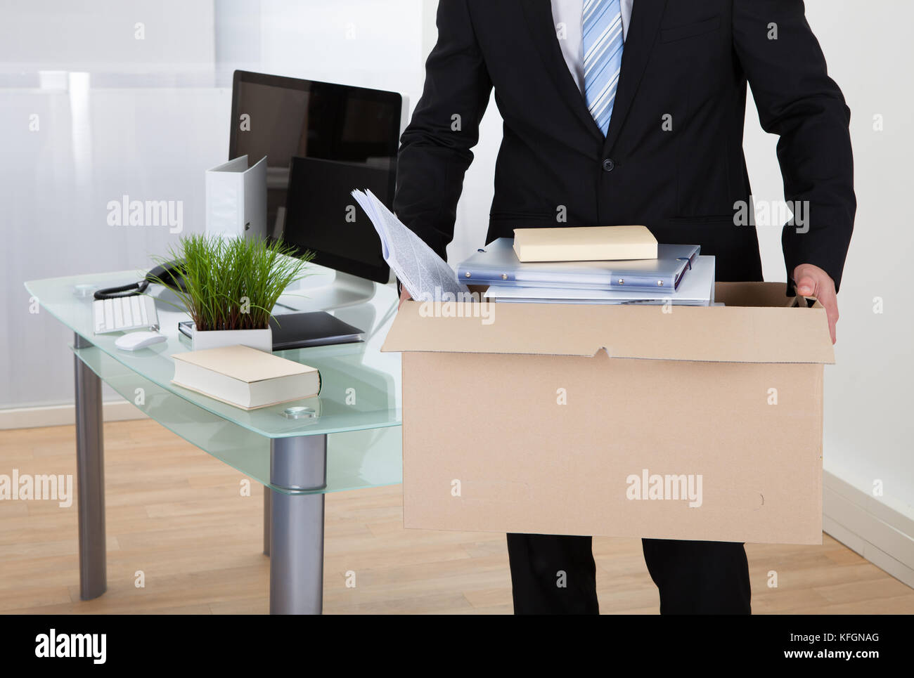 Businessman moving offices packing up all his personal belongings and files into a brown cardboard box - Stock Image