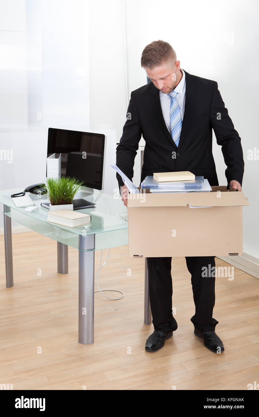 Dejected businessman made redundant or fired carrying a cardboard box full of his personal belongings with his head - Stock Image