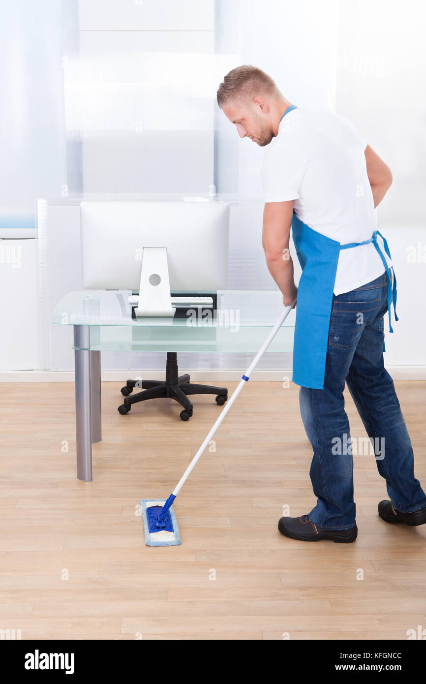 Handsome male janitor or cleaner cleaning the floor in an office building using a mop to wash the and disinfect Stock Photo