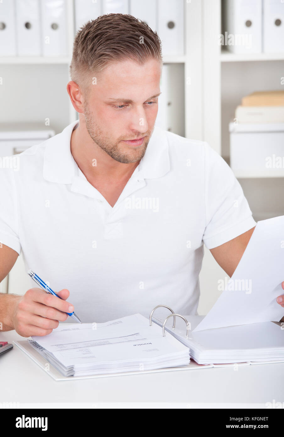 Businessman working at his desk in the office sitting writing notes in a short-sleeved white shirt - Stock Image