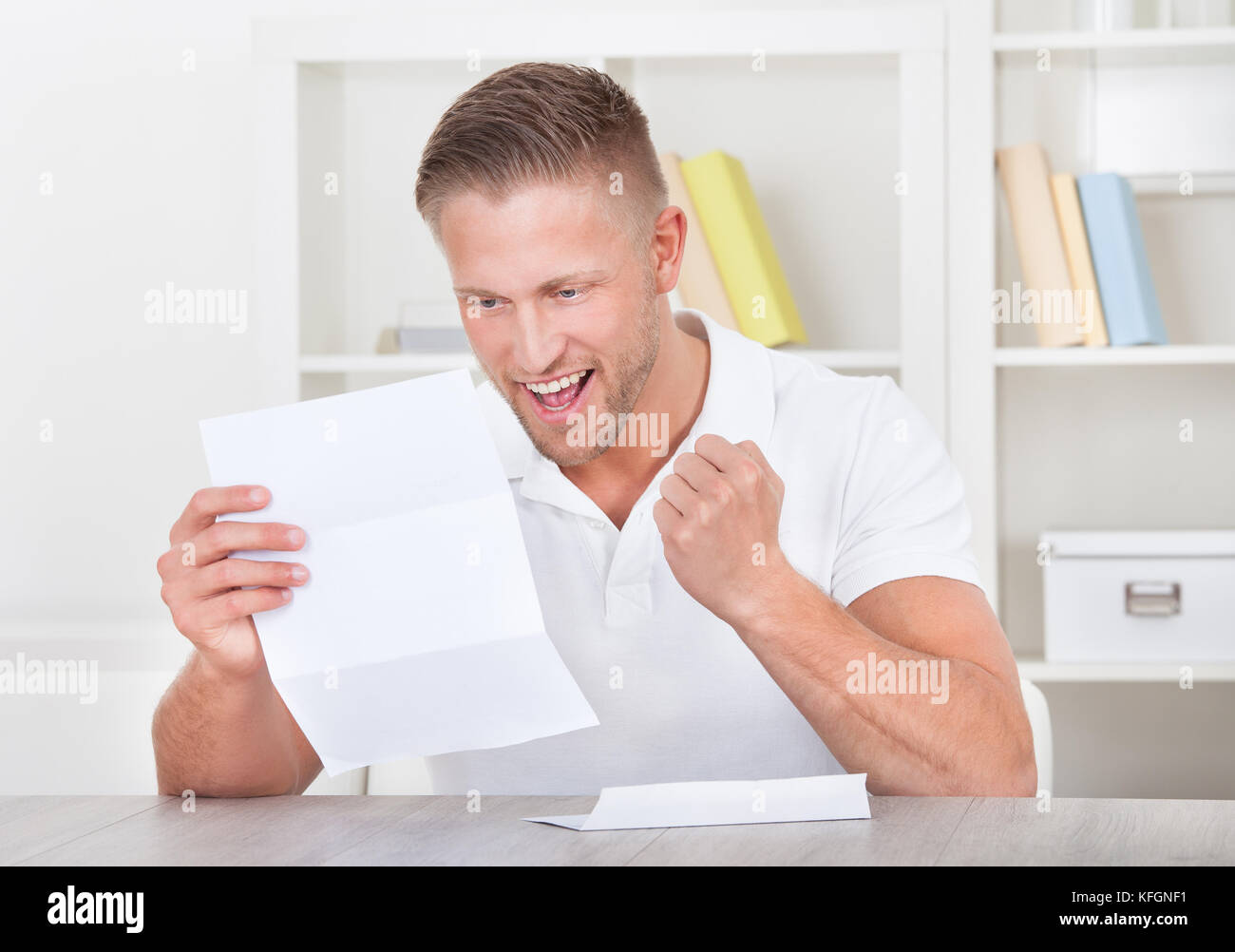 Man cheering in jubilation as he reads a letter punching the air with his fist as he reads the good news - Stock Image