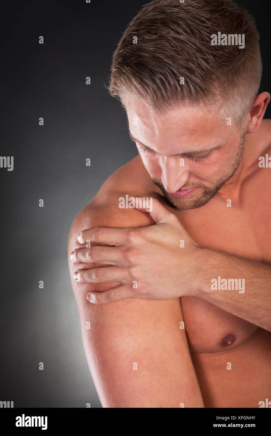 Muscular shirtless sportsman massaging his shoulder following a sprain or muscle injury looking down with a serious - Stock Image