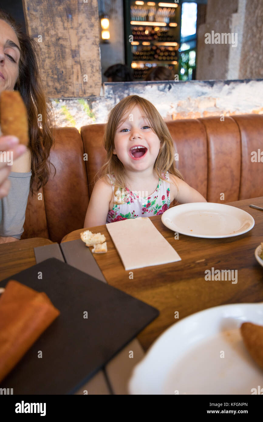 Four years age blonde girl looking and screaming next to woman mother sitting in brown leather sofa at restaurant - Stock Image
