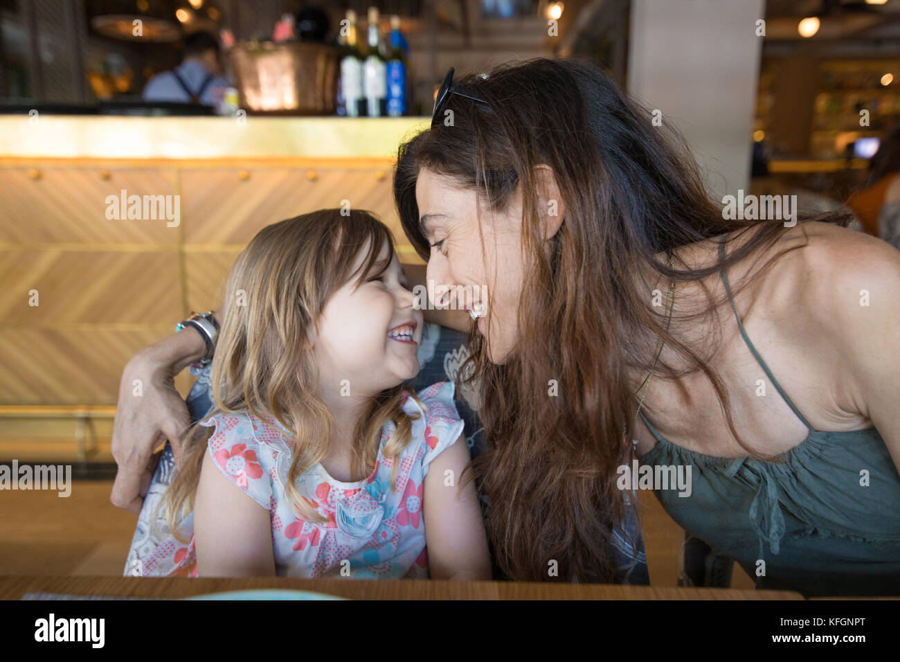 three years old blonde girl looking to woman mother laughing sitting in restaurant - Stock Image