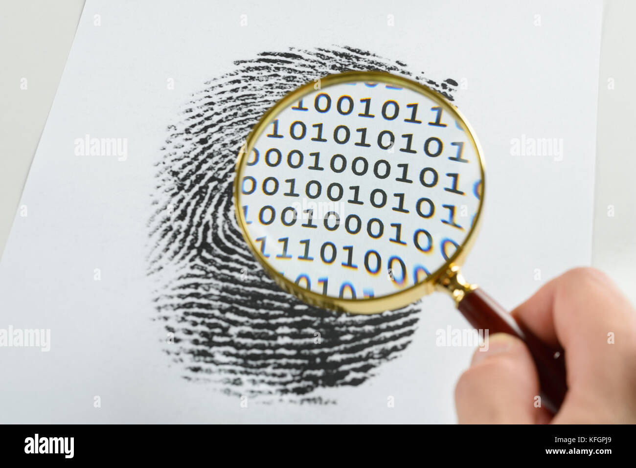 Person Hand With Magnifying Glass Over A Finger Print Revealing Binary Code Within The Print - Stock Image