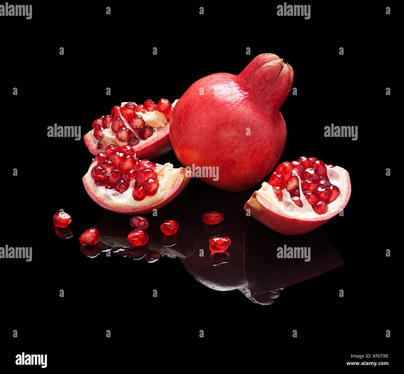 Pomegranate fruit with seeds and slices isolated on black glossy background with real reflection. - Stock Image