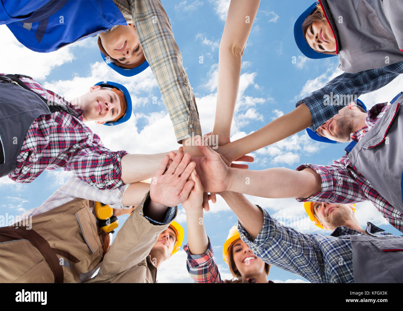 Directly below shot of multiethnic architects piling hands against sky Stock Photo
