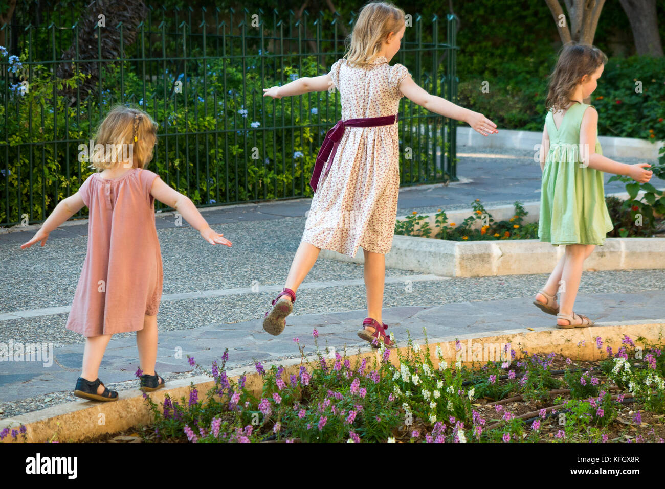 Three young sisters / girls / children / kids / kid aged 7, 3, & 5 years, on family holiday balance, run, & - Stock Image