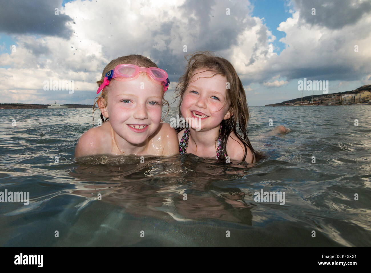 Sisters aged seven and five years old swim and play at Mellieha bay beach on the north coast of the main island - Stock Image
