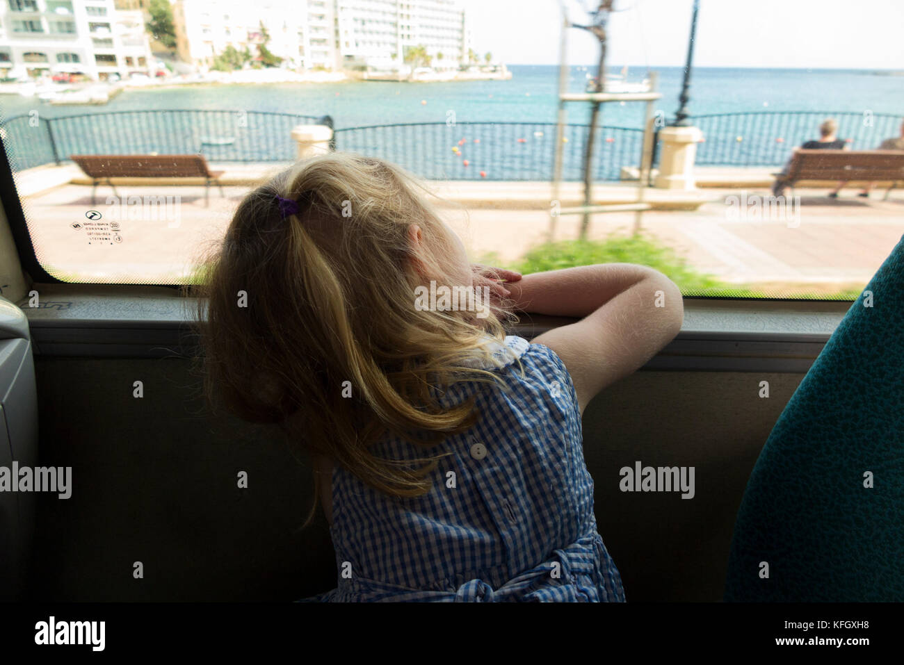 Three year old girl / child / passenger / passengers travelling on a public bus / using public transport in St Julians - Stock Image