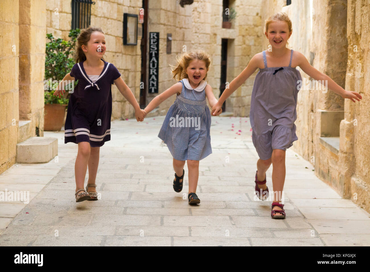 Three young sisters / girls / children / kids / kid aged 7, 3, & 5 years old, on a family holiday, run & - Stock Image