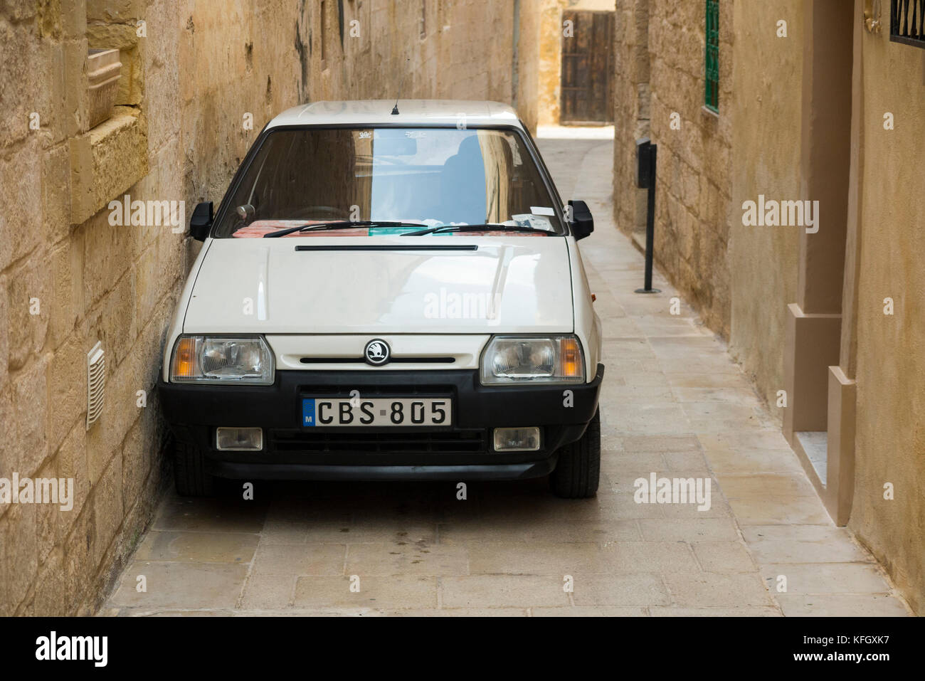 A Czechoslovakian Skoda car / vehicle parked too close to a wall in a narrow street / alley / road in the ancient - Stock Image