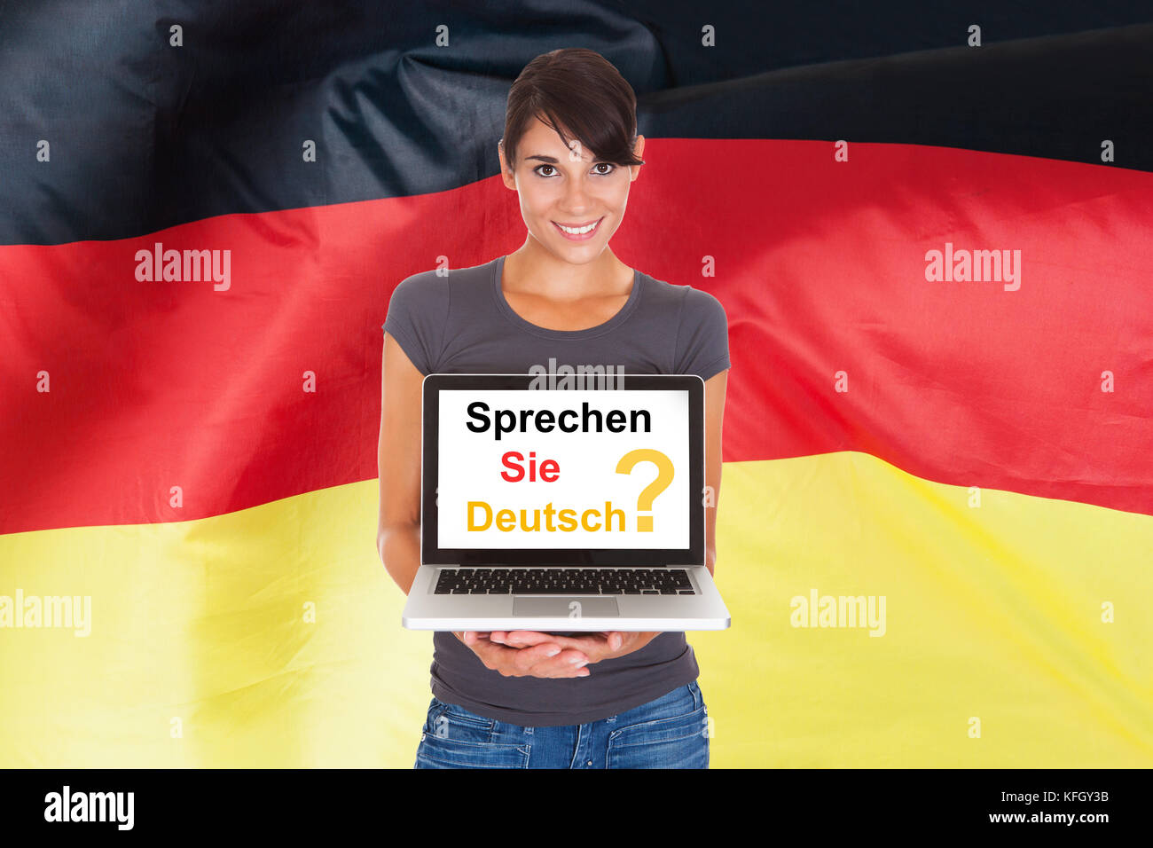 Young Woman Holding Laptop Asking Do You Speak German - Stock Image